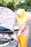 Mujer musulmán joven que comprueba el motor Imagen de archivo libre de regalías