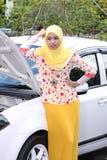 Mujer musulmán joven que comprueba el motor Imagen de archivo