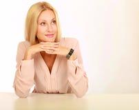 Mujer natural joven con la cara limpia que se sienta en la tabla blanca que se inclina en sus codos, sobre fondo Foto de archivo