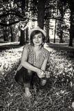 Mujer natural que presenta con los árboles en el contraluz soleado, descolorido Imagen de archivo