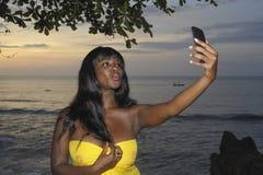 Mujer negra afroamericana atractiva en el vestido elegante del verano que toma la imagen o el vídeo del selfie en el teléfono móv Fotografía de archivo