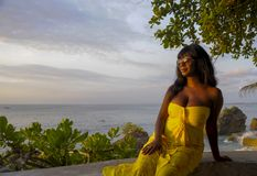 Mujer negra afroamericana atractiva y atractiva en la presentación elegante y elegante del vestido del verano relajada Foto de archivo