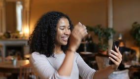 Mujer negra afroamericana joven que habla el vídeo elegante de la tecnología del teléfono que llama en café almacen de video