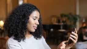 Mujer negra afroamericana joven que se divierte usando tecnología elegante del teléfono en café metrajes