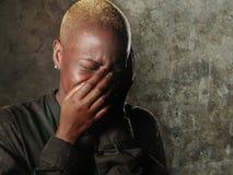 Mujer negra afroamericana triste y deprimida elegante joven que llora en cara de la cubierta de la desesperación con las manos qu foto de archivo