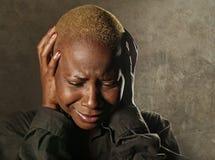 Mujer negra afroamericana triste y deprimida elegante joven que llora en la desesperación que se sostiene principal con las manos imagen de archivo