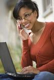 Mujer negra afuera en el teléfono celular y la computadora portátil Imagenes de archivo