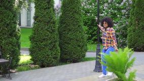 Mujer negra alegre con un peinado afro con los auriculares que camina abajo del baile y del canto MES lento de la calle almacen de video