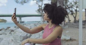 Mujer negra alegre que toma el selfie en orilla del mar metrajes