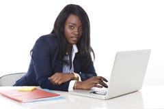 Mujer negra atractiva y eficiente de la pertenencia étnica que se sienta en mecanografiar del escritorio del ordenador portátil d Imagen de archivo libre de regalías