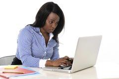 Mujer negra atractiva y eficiente de la pertenencia étnica que se sienta en mecanografiar del escritorio del ordenador portátil d Fotos de archivo libres de regalías