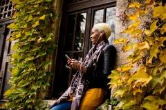 Mujer negra bastante joven con el teléfono móvil Imagenes de archivo