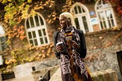 Mujer negra bastante joven con el teléfono móvil y el café Imágenes de archivo libres de regalías