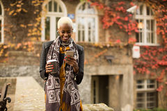 Mujer negra bastante joven con el teléfono móvil y el café Foto de archivo