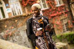 Mujer negra bastante joven con el teléfono móvil y el café Fotos de archivo