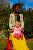 Mujer negra, bebé blanco Imagenes de archivo
