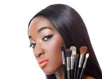 Mujer negra con el pelo recto que sostiene cepillos del maquillaje Foto de archivo libre de regalías