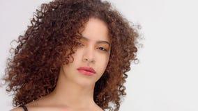 Mujer negra de la raza mixta con las pecas y el retrato del primer del pelo rizado con soplar del pelo metrajes