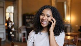 Mujer negra del afroamericano joven feliz que habla en el teléfono celular en café almacen de video