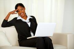 Mujer negra del asunto encantador en la computadora portátil Foto de archivo libre de regalías
