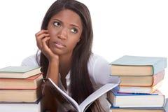 Mujer negra del estudiante universitario por la pila de libros Fotografía de archivo libre de regalías