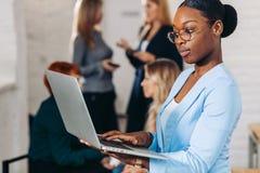 Mujer negra del negocio que ajusta su ordenador portátil, colocándose con los colegas detrás imagen de archivo libre de regalías