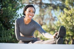Mujer negra deportiva hermosa con una sonrisa encantadora que estira él Imagenes de archivo