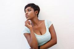 Mujer negra elegante que presenta contra el fondo blanco Imagen de archivo