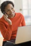 Mujer negra en el teléfono celular con la computadora portátil Foto de archivo libre de regalías