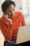 Mujer negra en el teléfono celular y la computadora portátil Imagenes de archivo