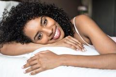 Mujer negra feliz en la cama que sonríe y que estira mirando el camer Imágenes de archivo libres de regalías
