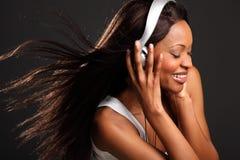 Mujer negra feliz hermosa que escucha la música Imagen de archivo libre de regalías