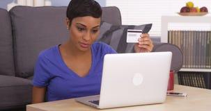 Mujer negra feliz que hace una compra en línea Foto de archivo libre de regalías