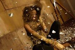 Mujer negra feliz que mira para arriba sorprendida el confeti del oro que cae sobre ella mientras que se sienta en piso Imagen de archivo