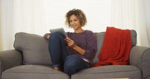 Mujer negra feliz que se sienta en el sofá usando la tableta Foto de archivo libre de regalías