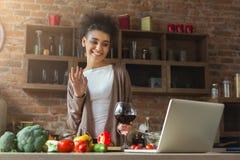 Mujer negra feliz que usa el ordenador portátil en interior moderno de la cocina Imágenes de archivo libres de regalías