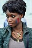 Mujer negra hermosa con la bandera francesa pintada en su mejilla Foto de archivo