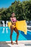 Mujer negra hermosa joven que presenta con el colchón inflable en el poolside foto de archivo libre de regalías