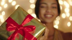 Mujer negra hermosa que mantiene la caja de regalo grande sus manos y sonrisa metrajes