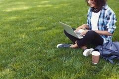 Mujer negra irreconocible que usa el ordenador portátil en parque imagenes de archivo