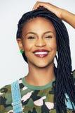 Mujer negra joven alegre en la ropa militar que lleva a cabo la cabeza imagenes de archivo