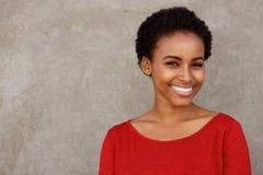 Mujer negra joven atractiva en la sonrisa roja de la camisa Fotos de archivo libres de regalías