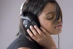 Mujer negra joven atractiva que escucha Imagen de archivo libre de regalías