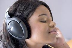 Mujer negra joven atractiva que escucha la música Imágenes de archivo libres de regalías