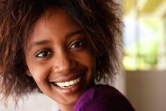 Mujer negra joven atractiva que sonríe con el pelo afro Fotografía de archivo libre de regalías