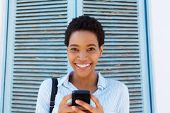 Mujer negra joven atractiva que sostiene el teléfono móvil Foto de archivo