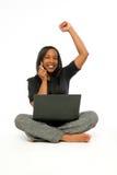 Mujer negra joven con el ordenador y el teléfono celular. Fotos de archivo