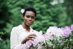 Mujer negra joven con el peinado afro en parque urbano Muchacha afroamericana que lleva la ropa casual entre las flores púrpuras fotos de archivo