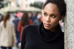 Mujer negra joven con el peinado afro que se coloca en backgrou urbano foto de archivo