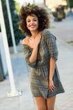 Mujer negra joven con el peinado afro que sonríe en backgroun urbano Fotografía de archivo